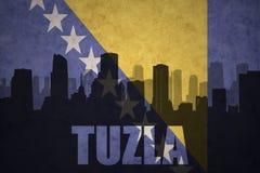 城市的抽象剪影有文本的图兹拉在葡萄酒波斯尼亚人旗子 库存图片