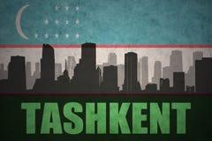 城市的抽象剪影有文本的塔什干在葡萄酒乌兹别克斯坦旗子 免版税库存图片