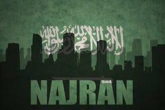 城市的抽象剪影有文本的奈季兰在葡萄酒沙特阿拉伯旗子 库存照片