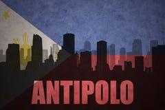 城市的抽象剪影有文本的安蒂波洛在葡萄酒菲律宾旗子 免版税库存图片