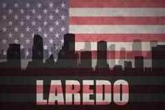 城市的抽象剪影有文本的拉雷多在葡萄酒美国国旗 库存照片