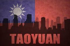城市的抽象剪影有文本的桃园在葡萄酒台湾旗子 免版税库存照片