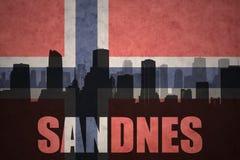 城市的抽象剪影有文本的桑内斯在葡萄酒挪威人旗子 免版税库存图片