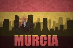 城市的抽象剪影有文本的穆尔西亚在葡萄酒西班牙人旗子 免版税图库摄影
