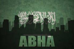 城市的抽象剪影有文本的艾卜哈在葡萄酒沙特阿拉伯旗子 免版税库存照片