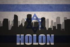 城市的抽象剪影有文本的霍隆在葡萄酒以色列旗子 图库摄影