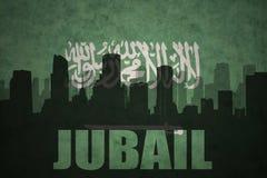 城市的抽象剪影有文本的Jubail在葡萄酒沙特阿拉伯旗子 免版税库存图片
