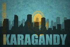城市的抽象剪影有文本的Karagandy在葡萄酒哈萨克斯坦旗子 免版税库存照片