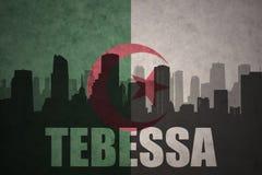 城市的抽象剪影有文本的Tebessa在葡萄酒阿尔及利亚人旗子 免版税库存照片
