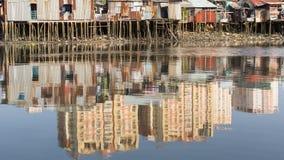 城市的贫民窟的看法从河的-新的高层建筑物的水反射的 免版税库存图片