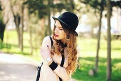 城市背景的微笑的年轻时髦行家女孩在室外的阳光下 库存图片