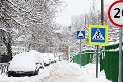 城市街道在冬天 用雪和汽车盖的路 免版税库存图片