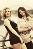 城市街道的两名愉快的年轻时尚妇女 库存照片