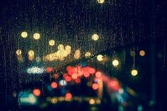 城市视图通过一个窗口在多雨夜 图库摄影