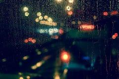 城市视图通过一个窗口在多雨夜 免版税库存照片