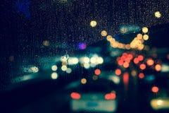 城市视图通过一个窗口在多雨夜 库存照片