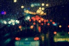 城市视图通过一个窗口在多雨夜 免版税库存图片