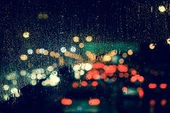 城市视图通过一个窗口在多雨夜 库存图片
