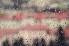 城市视图通过与雨的一个窗口下降 免版税库存图片