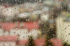 城市视图通过与雨的一个窗口下降 免版税库存照片
