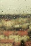 城市视图通过与雨的一个窗口下降 库存图片