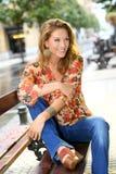 城市长凳的微笑的时髦妇女 库存图片