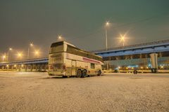 城市间的公共汽车站在一个多雪的冬天城市在晚上停放 免版税库存图片