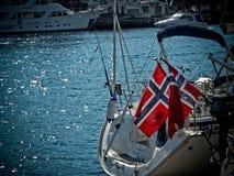 城市风景在与挪威的旗子的一个晴天游艇的 免版税库存照片
