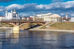 城市风景,在桥梁附近的河岸是教会,剧院,蓝色多云天空 免版税库存图片