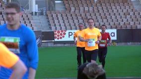 城市马拉松的参加者在体育场完成 股票录像
