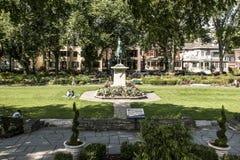 13城市魁北克 09 2017个古铜色雕象密室乔安娜D弧-圣贞德战争纪念建筑在一个五颜六色的庭院里在一个晴天 免版税库存图片