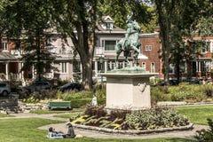 13城市魁北克 09 2017个古铜色雕象密室乔安娜D弧-圣贞德战争纪念建筑在一个五颜六色的庭院里在一个晴天 免版税库存照片