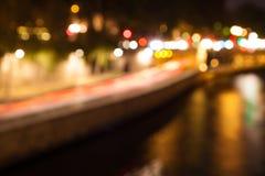 城市Bokeh点燃与反映在河 库存图片