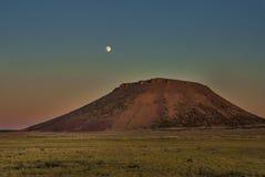 域小山和月亮日落 免版税库存照片
