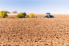 培养一个大领域的拖拉机在晴朗的秋天天 库存图片
