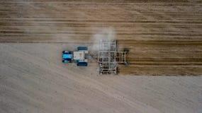 培养领域的拖拉机在春天,耕种是土壤的农业准备由机械鼓动各种各样输入 免版税图库摄影