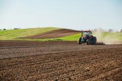 培养领域的拖拉机在春天 免版税库存图片