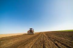 培养领域的拖拉机在春天 免版税库存照片