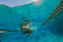 培训游泳的妇女在水面下 免版税库存照片