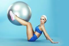 培训 横跨地 运动服的妇女有健身球的 免版税库存图片