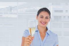 培养一杯香槟的深色的女实业家 免版税库存图片