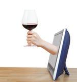 培养大玻璃用红葡萄酒的手倾斜电视 库存图片