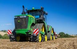 培养英国庄稼领域的现代约翰Deere caterpilla拖拉机 库存照片