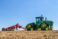 培养英国庄稼领域的现代约翰Deere caterpilla拖拉机 免版税图库摄影