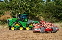 培养英国庄稼领域的现代约翰Deere caterpilla拖拉机 免版税库存照片
