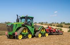 培养英国庄稼领域的现代约翰Deere caterpilla拖拉机 库存图片