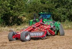 培养英国庄稼领域的现代约翰Deere caterpilla拖拉机 免版税库存图片