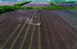 培养领域的拖拉机在春天,鸟瞰图 库存照片
