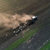 培养领域的拖拉机在春天,鸟瞰图 免版税库存照片