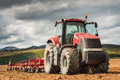 培养领域的红色拖拉机在蓝天下 库存照片